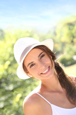 beautycare: Portrait of beautiful woman with hat in park