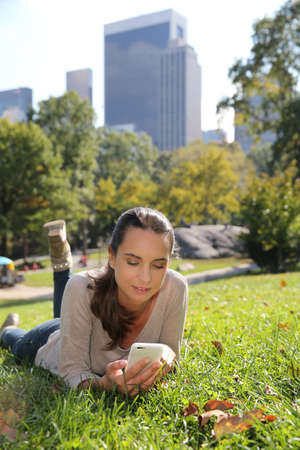 Young woman in Central Park using smartphone photo