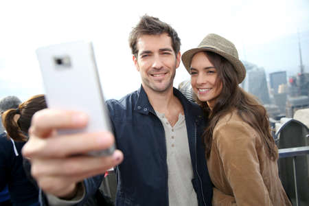 Couple taking picture with smartphone, skyline in background photo