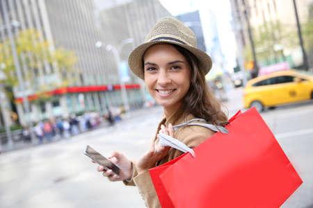 tourist vacation: Shopping ragazza con la borsa rossa e smartphone a Manhattan Archivio Fotografico