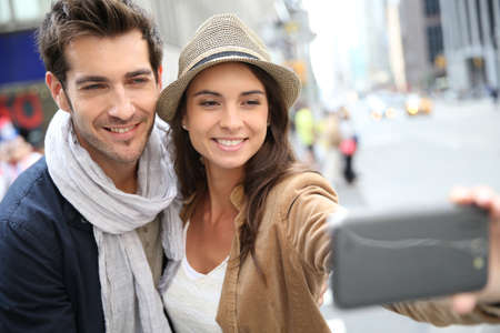Couple in Manhattan taking picture with smartphone photo