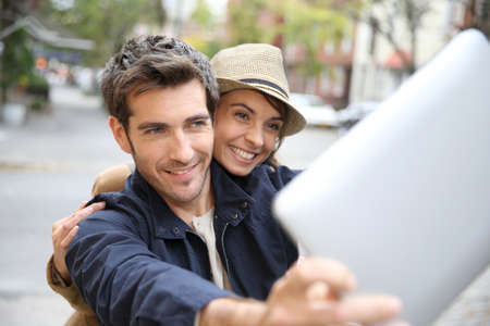 selfy: Cheerful couple taking picture with tablet