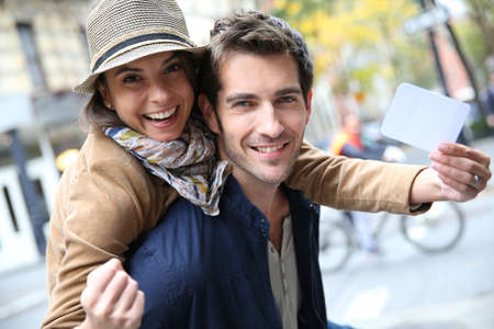 greenwich: Cheerful couple showing New York City pass