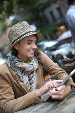 trendy girl: Trendy girl sitting at coffee shop and using tablet Stock Photo