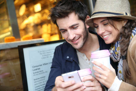 Couple in coffee shop connected with smartphone photo