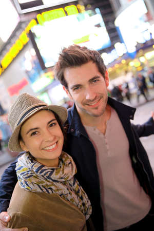 Couple standing in Time Square quarter by night photo