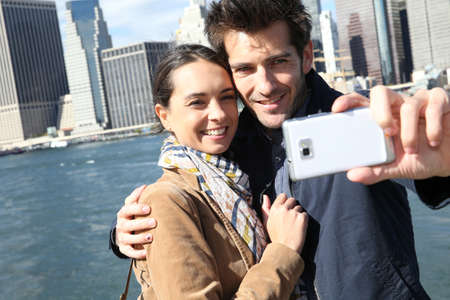Couple taking picture with Manhattan skyline in background photo