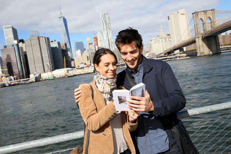 Couple of tourists reading New York city guide Stock Photo
