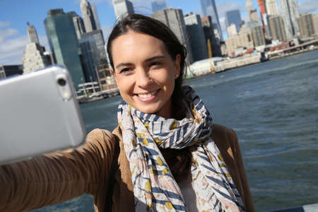Brunette girl making selfy with Manhattan in background photo