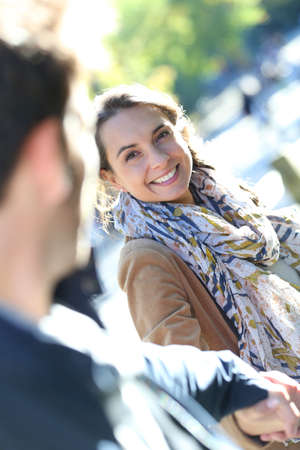 new love: Portrait of cheerful girl pulling boyfriend by arm in Central Park Stock Photo