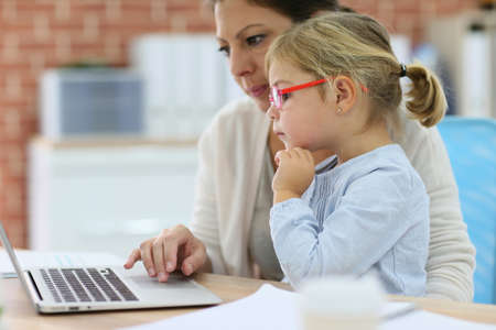 homeoffice: Mother working at home-office with daughter on her lap