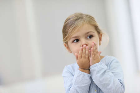 Cute little girl blowing kisses away photo