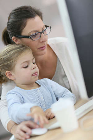 homeoffice: Mother working in home-office, daughter on her lap Stock Photo