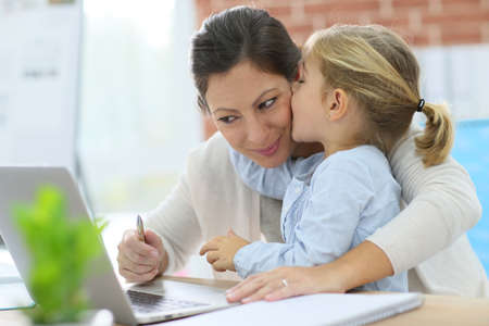 work from home: Little girl giving kiss to her mom while working from home Stock Photo