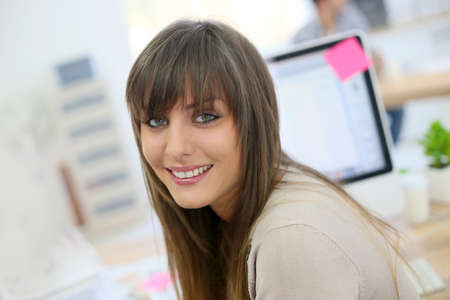 Portrait of young woman sitting in front of desktop computer photo