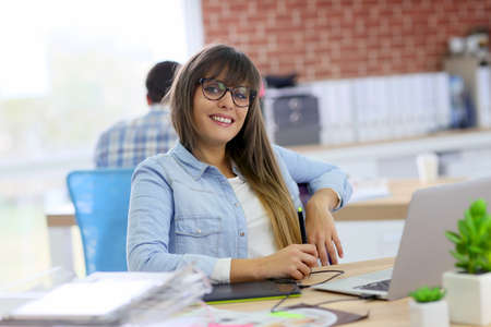 Young woman working with graphic tablet in office photo