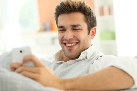 Casual guy using smartphone, relaxing in couch photo