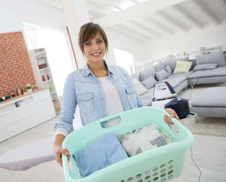 Young home service woman holding basket of folded laundry photo