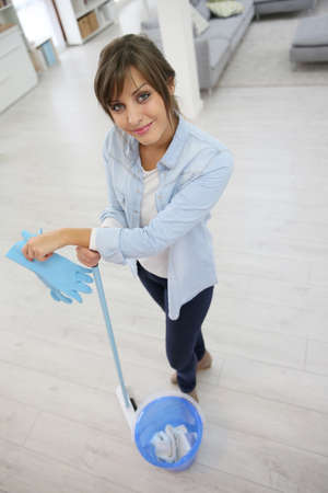 mopping: Young housekeeper standing with mopping equipment Stock Photo