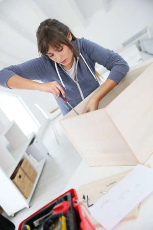 doityourself: Single young woman assembling pieces of new furniture Stock Photo