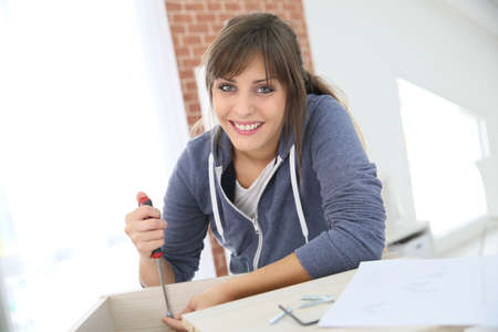 single woman: Single young woman assembling pieces of new furniture Stock Photo