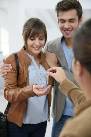 getting together: Happy young couple getting key of their new place Stock Photo