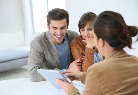 saleswoman: Young couple meeting real estate agent Stock Photo
