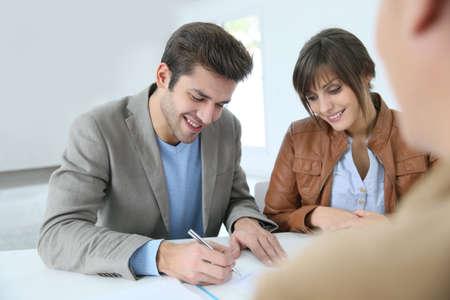 firmando: Pareja joven en el acuerdo de propiedad de la agencia de firma de bienes raíces