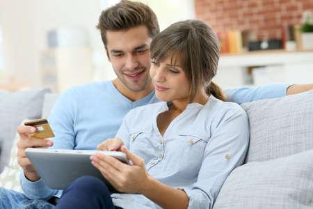 parejas: Pareja joven de compras en Internet con la tableta