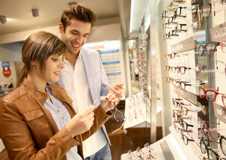 Young couple in optical shop trying eyeglasses Stockfoto