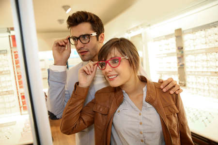 Couple in optical shop choosing eyeglasses