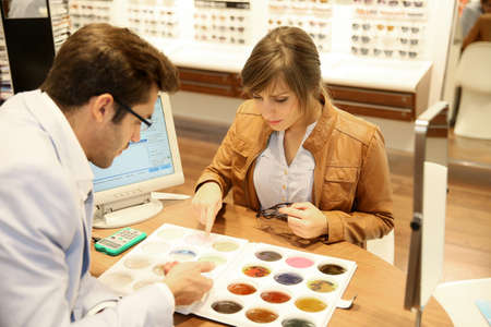 Woman with optician choosing spectacle lenses colour photo