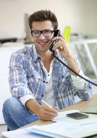 answering phone: Trainee in office talking on the phone