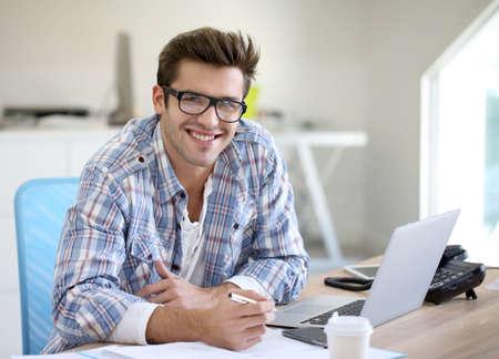 secretaria: Hombre joven en la oficina que trabaja en la computadora port�til Foto de archivo