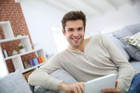 websurfing: Man sitting in couch and websurfing on internet Stock Photo