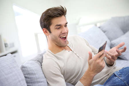 surprised man: Man with smartphone being surprised as reading message