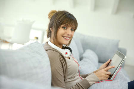 Young woman with headphones websurfing on tablet photo