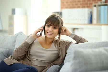 Portrait of young woman at home talking on mobile phone Stock Photo