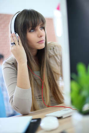 Young woman at work using headphones in front of desktop photo