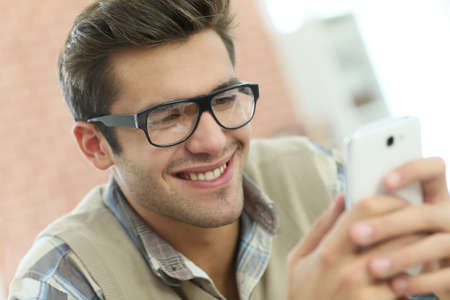 officeworker: Young man connected on internet with smartphone Stock Photo