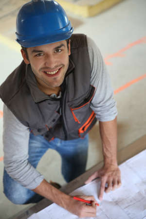 building safety: Construction worker checking blueprint