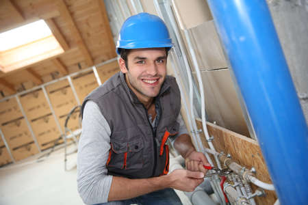 Plumber working in home being renovated Stock Photo
