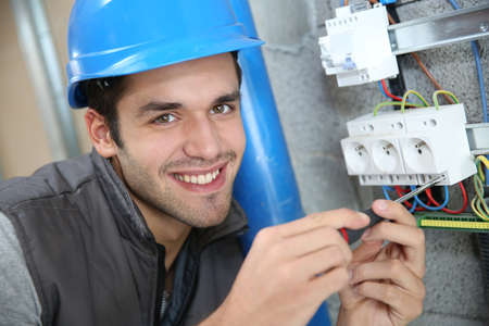 controling: Young electrician working on building site