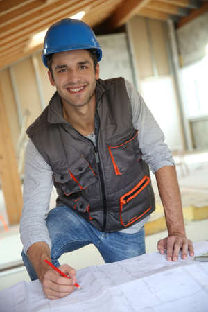 controling: Construction worker checking blueprint