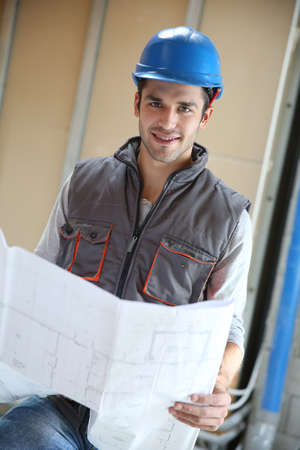 controling: Contractor reading contruction blueprint on site