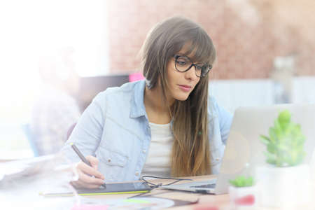 graphic tablet: Young woman working with graphic tablet in office