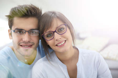 couple on couch: Portrait of young couple with eyeglasses on