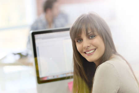 Student girl sitting in front of desktop computer photo