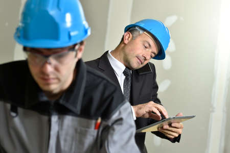 controling: Young craftsman with supervisor in background Stock Photo