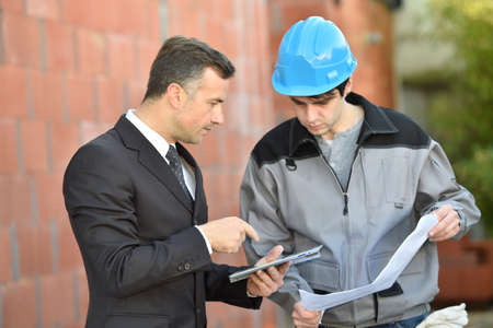 controling: Contractor on building site checking different points with worker